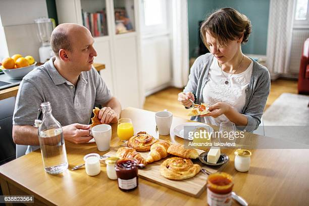 Happy french couple eating breakfast at home
