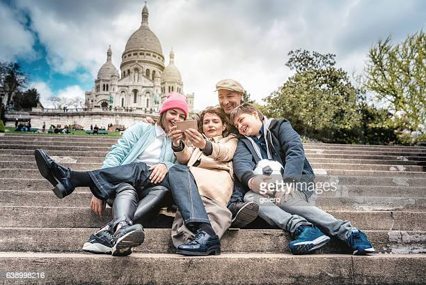 happy french family taking selfie on monmartre stairs in Paris