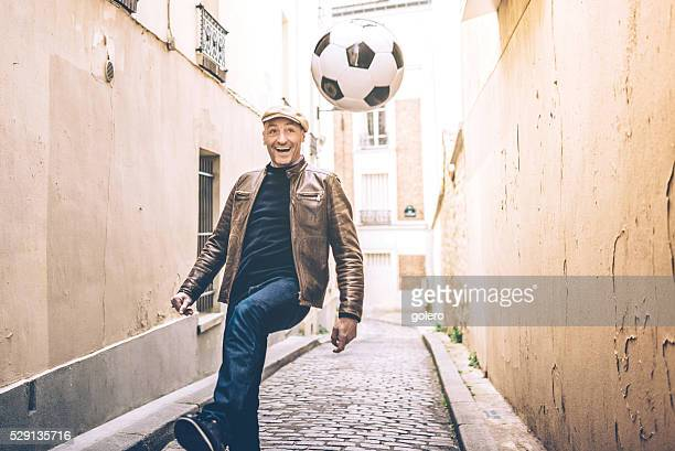 happy french man playing soccer in Paris street