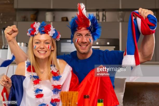 couple de fan heureux football français à la maison - marquer photos et images de collection