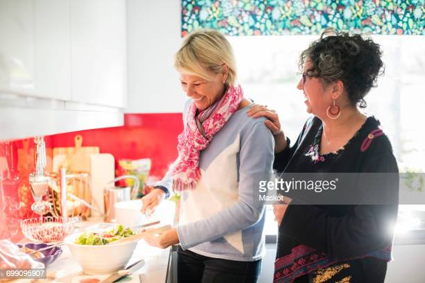 Happy friend talking to woman while preparing salad in brightly lit kitchen