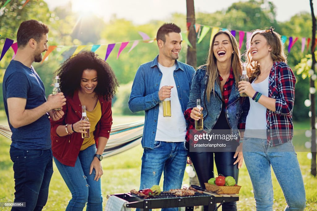 Happy friends are doing barbecue in the park and making fun : Stock Photo