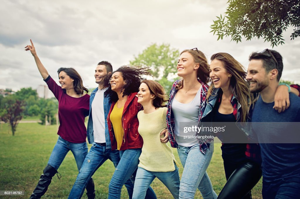 Happy friends are wlaking ahead arm in arm : Stock Photo