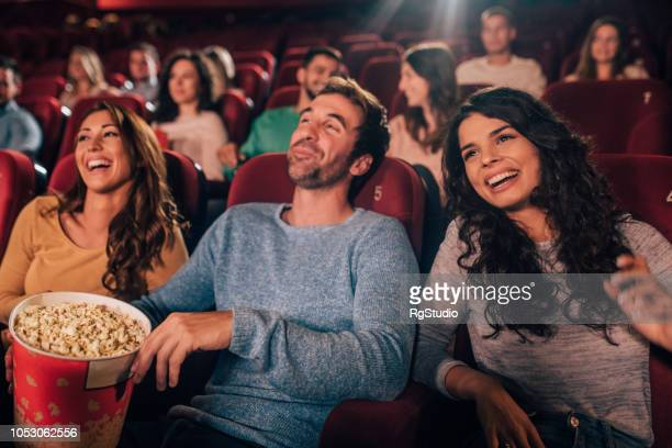 happy friends at cinema - comedy film stock photos and pictures