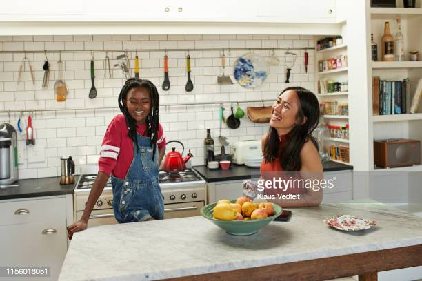 happy friends at kitchen island - roommate stock pictures, royalty-free photos & images