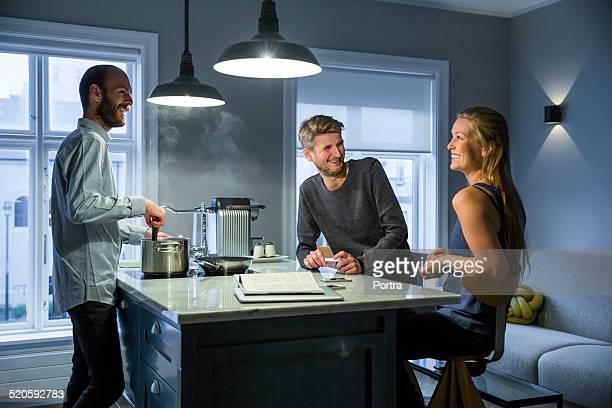 Happy friends at kitchen island