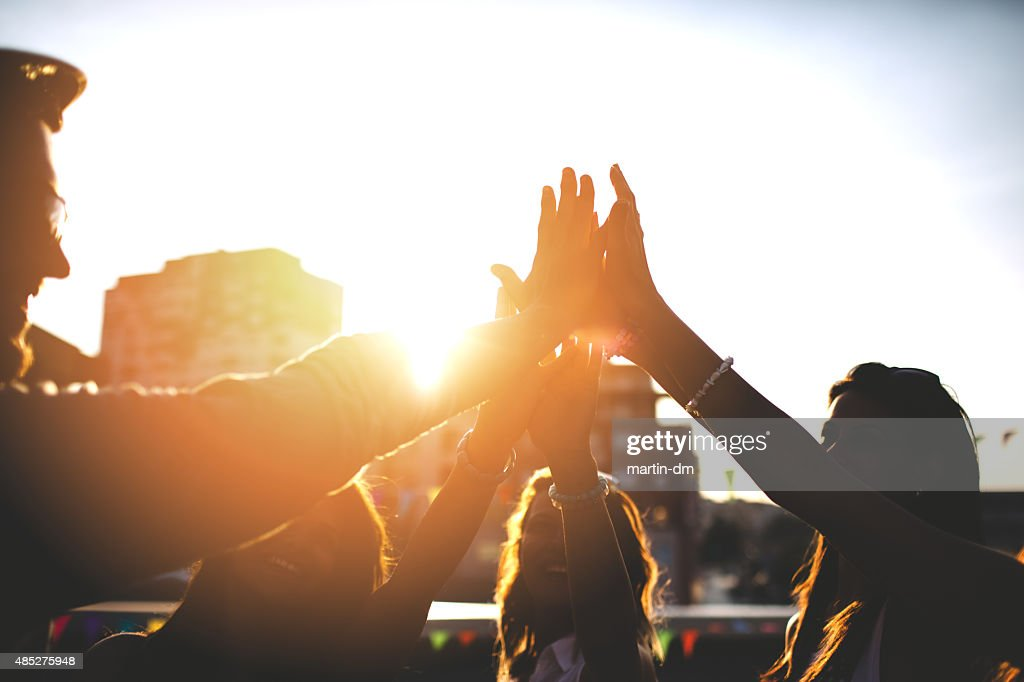 Happy friends at the rooftop doing high five : Stock Photo