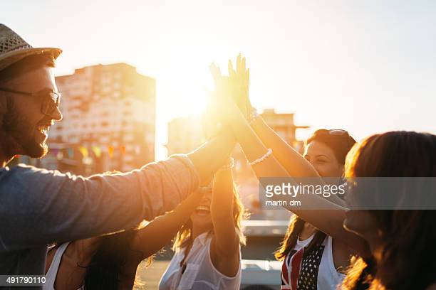 happy friends at the rooftop doing high five - tegenlicht stockfoto's en -beelden