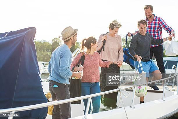 Happy friends boarding yacht against sky