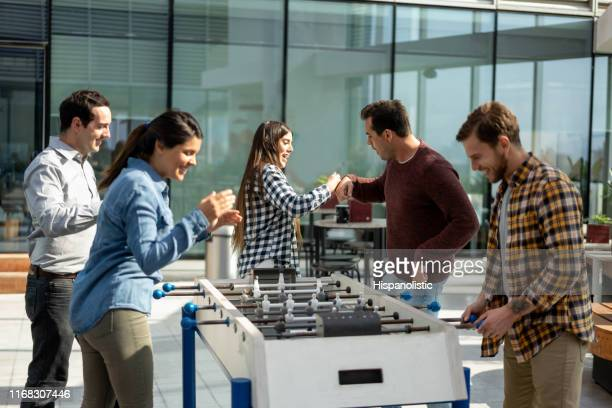Happy friends celebrating a score during a foosball game at the office
