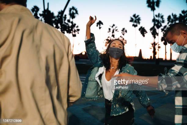 幸せな友人が一緒に祝い、踊る - カリフォルニア州 ベニス ストックフォトと画像