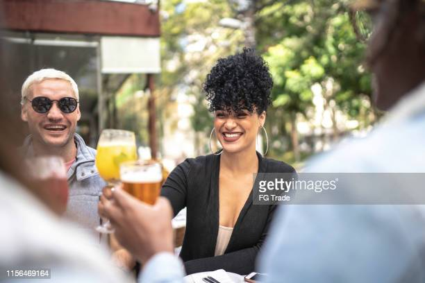 happy friends celebrating and toasting at bar - part of a series stock pictures, royalty-free photos & images