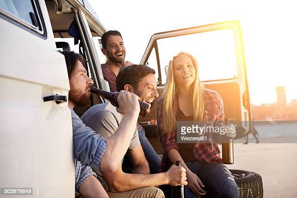 Happy friends celebrating at minivan
