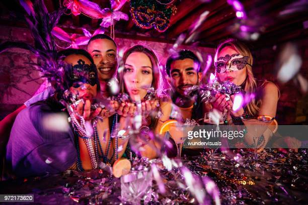 happy friends celebrating mardi gras and blowing confetti at party - mardi gras party stock photos and pictures