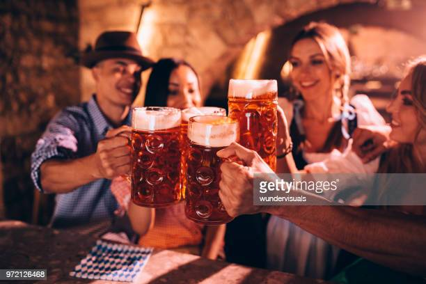 happy friends celebrating oktoberfest and toasting with beer - munich stock pictures, royalty-free photos & images