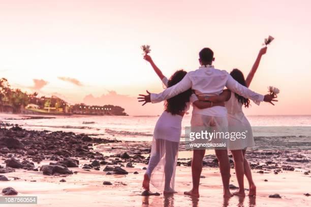 amigos felizes comemorando o reveillon na praia, abraçando um ao outro e segurando flores brancas. praia do paraiso, mosqueiro - noite de réveillon - fotografias e filmes do acervo
