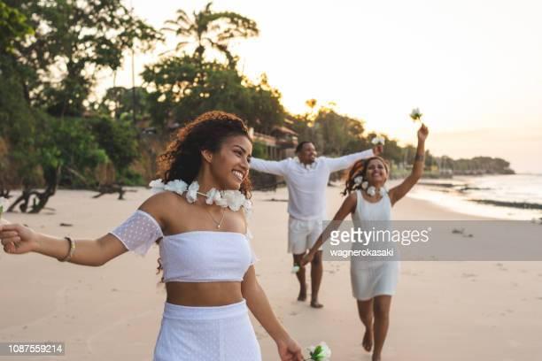 amigos felizes comemorando o reveillon na praia, correndo e segurando flores brancas. praia do paraiso, mosqueiro - comemoração conceito - fotografias e filmes do acervo