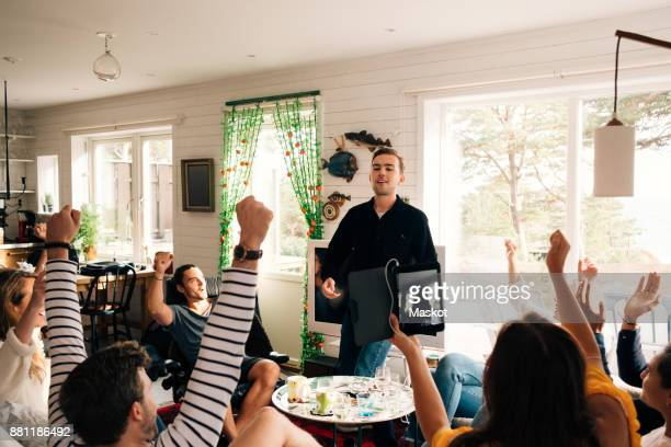 Happy friends celebrating success of man in cottage