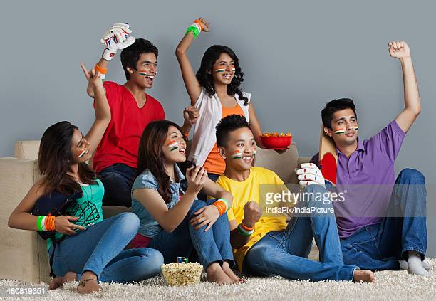 Happy friends cheering while watching cricket match in living room