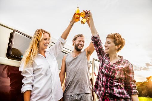 Happy friends clinking beer bottles at a van in rural landscape - gettyimageskorea