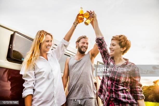 happy friends clinking beer bottles at a van in rural landscape - getränk stock-fotos und bilder