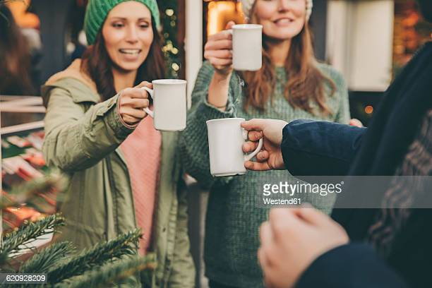 Happy friends clinking cups of hot punch on the Christmas Market