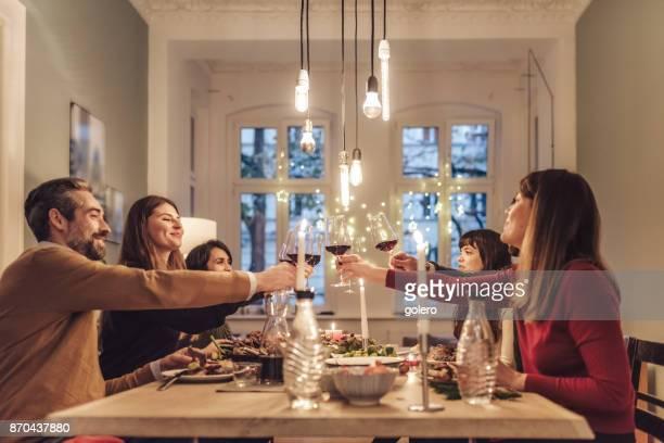 glückliche freunde klirren weingläser am weihnachtstisch - christmas stock-fotos und bilder