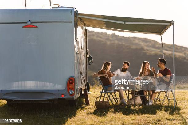happy friends communicating at picnic table by the camp trailer in summer day. - camper van stock pictures, royalty-free photos & images