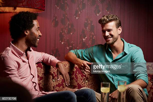 happy friends communicating on sofa at nightclub - face to face stock pictures, royalty-free photos & images