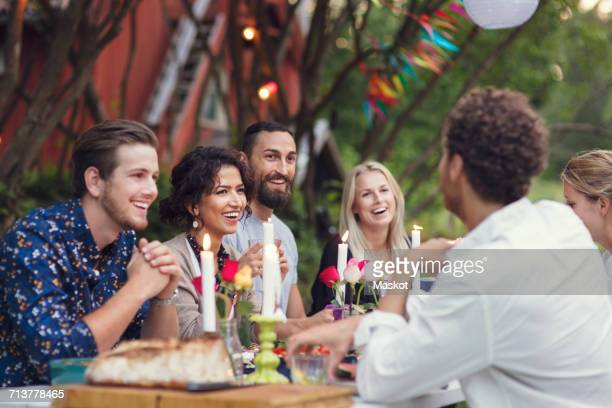 Happy friends communicating while enjoying meal at garden party