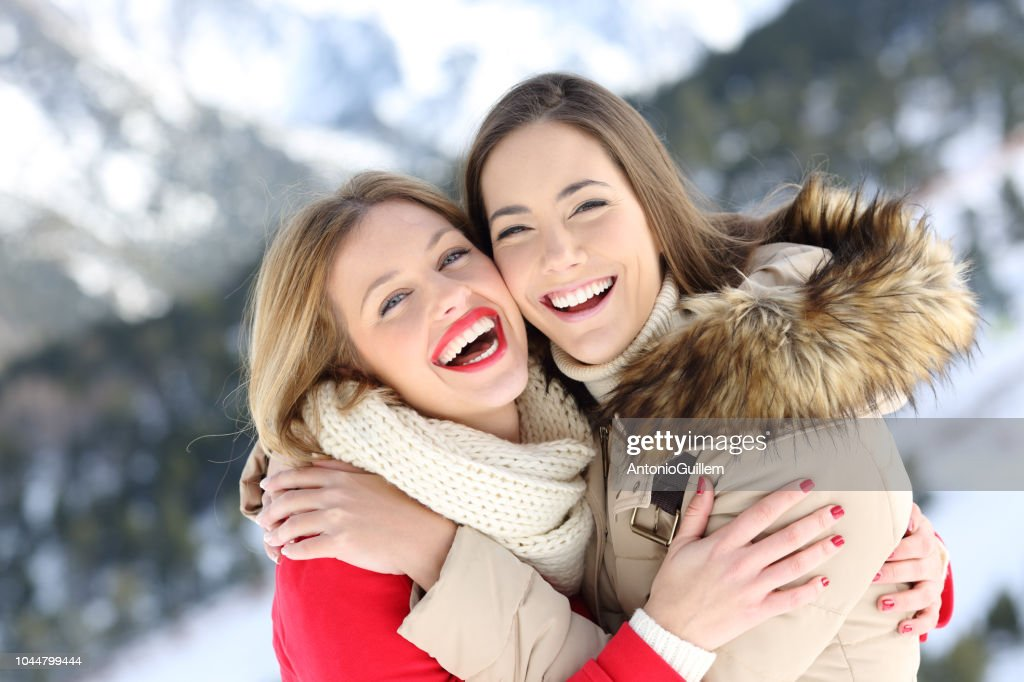 Happy friends cuddling and posing in winter holiday : Stock Photo