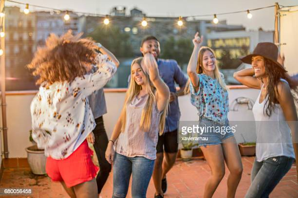 Happy friends dancing while enjoying terrace party