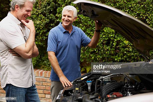 happy friends discussing over broken down car - only mature men stock pictures, royalty-free photos & images