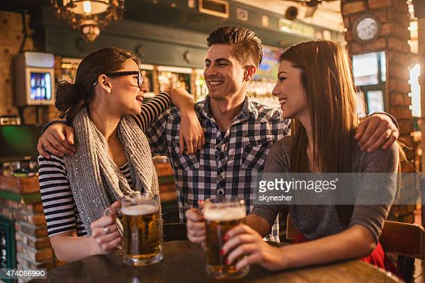Happy friends drinking beer and having fun in a bar.