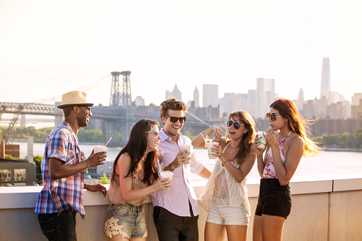Happy friends drinking iced coffee while standing on building terrace against Williamsburg Bridge - gettyimageskorea