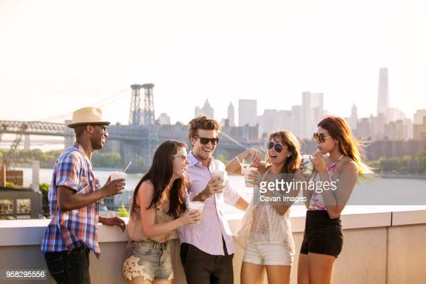 happy friends drinking iced coffee while standing on building terrace against williamsburg bridge - cavan images foto e immagini stock
