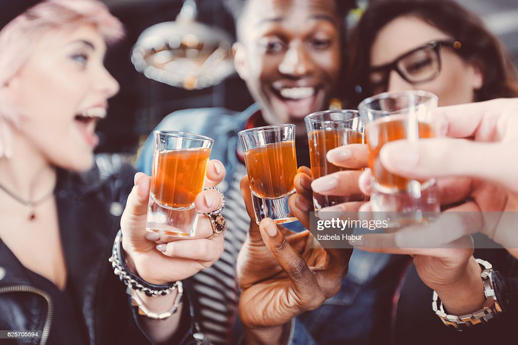 Happy friends drinking shots : Stock Photo