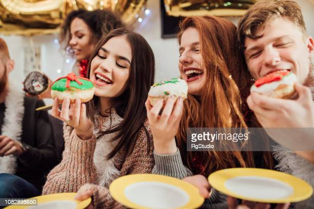happy friends eating cookies - teenagers only stock pictures, royalty-free photos & images