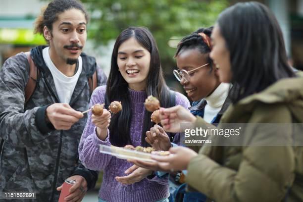 happy friends eating parcel takoyaki in city - takoyaki stock pictures, royalty-free photos & images
