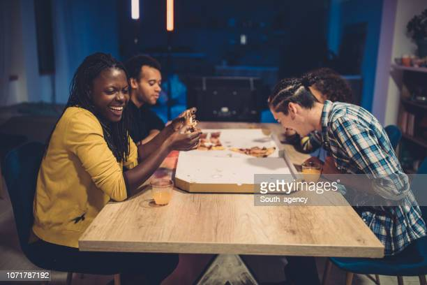happy friends eating pizza - guest stock pictures, royalty-free photos & images