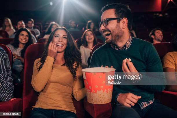 amici felici che mangiano popcorn al cinema - prima cinematografica foto e immagini stock
