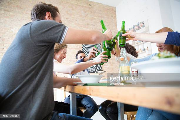 Happy friends eating together clinking beer bottles