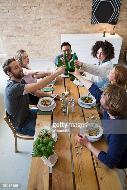 Happy friends eating together clinking beer bottles