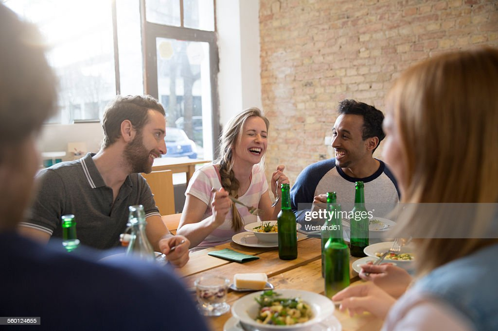 Happy friends eating together : Stock Photo
