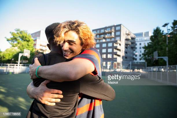 happy friends embracing each other while playing in sports field - generation z stock pictures, royalty-free photos & images