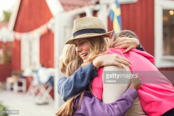 Happy friends embracing in back yard