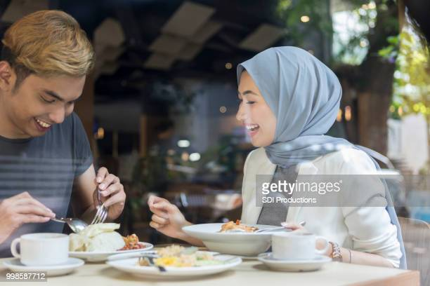 happy friends enjoy meal together - muslim couple stock pictures, royalty-free photos & images