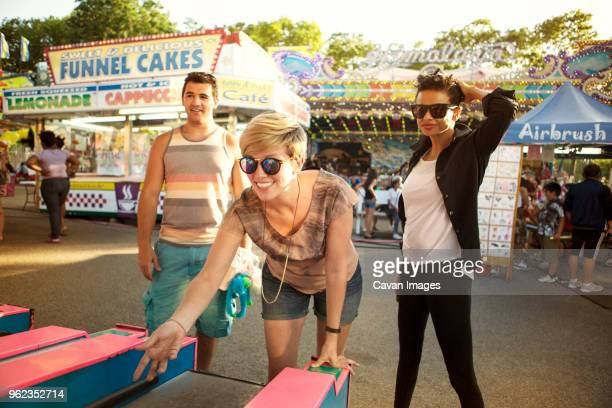 happy friends enjoying at amusement park arcade - traveling carnival stock pictures, royalty-free photos & images