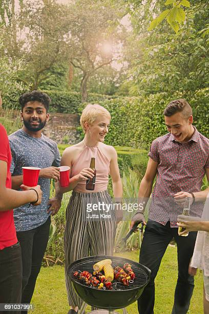 happy friends enjoying barbecue party at yard - metal grate stock photos and pictures
