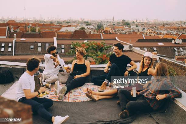 happy friends enjoying beer while sitting at terrace during rooftop party in city - men friends beer outside stock pictures, royalty-free photos & images